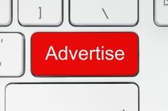 Roter Knopf mit adverise Wort auf der Tastatur Stockbilder