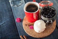 Roter Kreis, Blaubeeren und Eibisch auf Jeanshintergrund, modisches Frühstück Stockfotografie