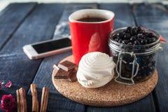 Roter Kreis, Blaubeeren und Jogurt in den Hintergrundjeans, modisches Frühstück mit Smartphone und Zimt Stockfotos