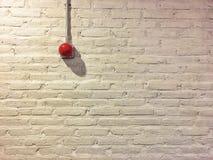 Roter Kreisfeuermelder auf weißer Backsteinmauer der Weinlese lizenzfreies stockbild