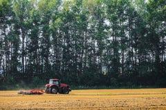 Roter Landwirtschaftstraktor funktioniert auf dem Gebiet Scheibenegge für die Zerquetschung von Stoppeln Lizenzfreies Stockbild