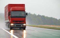 Roter Lastwagen auf nasser Straße Lizenzfreie Stockfotos