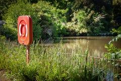 Roter Leben-Bojen-Ring durch See Lizenzfreies Stockfoto