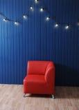 Roter Ledersessel auf einem Hintergrund der blauen Wand mit Retro- Girlande von Glühlampen Beschaffenheit für den Entwurf Stockbilder