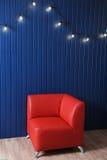 Roter Ledersessel auf einem Hintergrund der blauen Wand mit Retro- Girlande von Glühlampen Beschaffenheit für den Entwurf Lizenzfreies Stockbild
