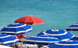 Roter Leibwächtersonnenschutzregenschirm auf Blau stockfoto