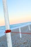 Roter Leinenpfosten mit Morgenlichtsteinen auf Strand nah an dem s Stockbilder
