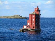 Roter Leuchtturm, der im Meer steht stockfotos