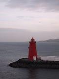 Roter Leuchtturm am Ende der schwarzen Steinanlegestelle Lizenzfreie Stockfotografie