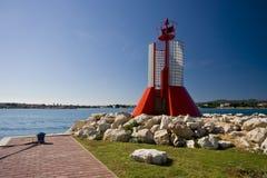 Roter Leuchtturm unter den Felsen Stockbild