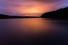 Roter Lichtreflex auf einem See in einem großartigen Sonnenuntergang lizenzfreies stockfoto
