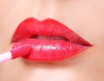 Roter Lippenstift. Lipgloss auf sexy Lippen und Bürste. Stockfotografie