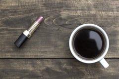 Roter Lippenstift und Tasse Kaffee auf Holztisch Stockbild