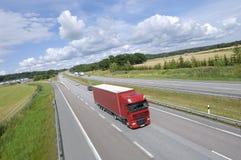 Roter LKW, der auf Autobahn beschleunigt lizenzfreie stockbilder