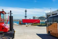 Roter LKW, der in den Griff eines Frachtschiffs einsteigt Stockfotografie