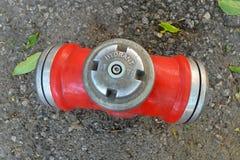 Roter Metallhydrant auf einem Hintergrund der Draufsicht des alten grauen Asphalts stockfotografie