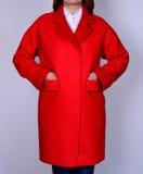 Roter modischer Mantel mit Taschen auf grauem Hintergrund Oberbekleidung, Sammlung von Frühling 2017 Lizenzfreie Stockbilder
