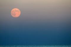 Roter Mond, der über das blaue Meer steigt Lizenzfreie Stockbilder