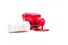 Roter Nagellack, der aus umgeworfener Flasche gießt Stockfoto