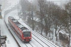 Roter Nahverkehrszug in Schneefälle in der Schweinfurt-Stadt Stockbilder