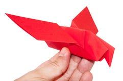 Roter Origamivogel, der auf der Hand sitzt Stockbilder
