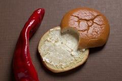 Roter Pfeffer-und Brötchen-Lebensmittel in zwei halben Stücken Lizenzfreie Stockbilder