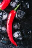 Roter Pfeffer und Eis auf einem schwarzen hölzernen Hintergrund, neue warme Küche auf Weinlesetabelle, friert kaltes Würfeleis, S lizenzfreie stockfotografie