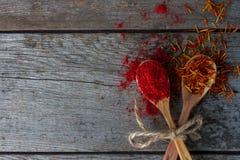 Roter Pfeffer und Safran in den hölzernen Löffeln auf rustikaler Tabelle, bunte indische Gewürze Stockfotos