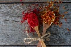 Roter Pfeffer und Safran in den hölzernen Löffeln auf rustikaler Tabelle, bunte indische Gewürze Lizenzfreies Stockbild