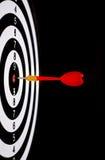 Roter Pfeilpfeil, der in der Zielmitte der Dartscheibe schlägt Lizenzfreie Stockfotografie