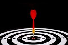 Roter Pfeilpfeil, der in der Zielmitte der Dartscheibe schlägt Stockfoto