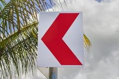 Roter Pfeilzeiger auf tropischem Hintergrund Straßenrand mit Palme verlässt und bewölkter Himmel Stockfotografie