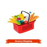 Roter Plastikeinkaufskorb voll von Lebensmittelgeschäften Stockfoto