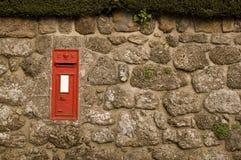 Roter Postbox in der englischen Dorf-Wand Lizenzfreie Stockfotografie
