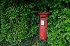 Roter Postbox umgeben durch grüne Blätter Lizenzfreie Stockfotos