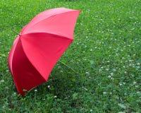 Roter Regenschirm auf dem Hintergrund des grünen Grases Lizenzfreies Stockfoto