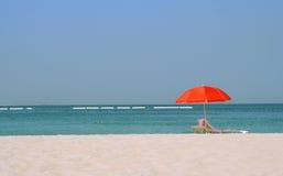 Roter Regenschirm auf einem Sandstrand an der Küste Lizenzfreies Stockfoto