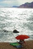 Roter Regenschirm auf einem Sonnenuntergangstrand Lizenzfreie Stockfotografie
