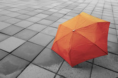 Roter Regenschirm auf nassem Boden Lizenzfreies Stockbild
