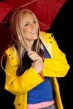 Roter Regenschirm der Frau und gelbe Jacke glücklich lizenzfreies stockbild