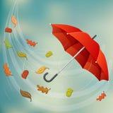 Roter Regenschirm im Wind mit Herbstblatt Lizenzfreie Stockfotografie