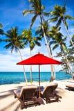 Roter Regenschirm und Stühle auf Sand setzen in den Tropen auf den Strand Stockbild