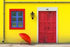 Roter Regenschirm vor Retro- Weinlese-europäischem Wohnungsbau mit gelber Wand, roter Tür und blauem Windows, schmales Straßenbil lizenzfreie abbildung