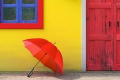Roter Regenschirm vor Retro- Weinlese-europäischem Wohnungsbau mit gelber Wand, roter Tür und blauem Windows, schmales Straßenbil stockbild