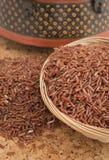 Roter Reis auf Korkenbrett und ethnischem Hintergrund Stockfotografie