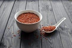 Roter Reis in einer keramischen Schüssel mit Löffel gegen dunklen hölzernen Hintergrund lizenzfreies stockbild