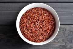 Roter Reis in einer kleinen keramischen Schüssel gegen dunklen rustikalen hölzernen Hintergrund lizenzfreies stockfoto