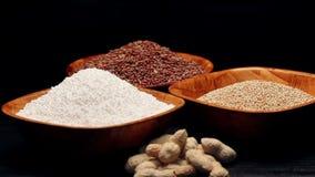 Roter Reis, Hirsekörner, Tapioka perlt in den kleinen Schüsseln und in einem Stapel von Erdnüssen und dreht sich stock footage