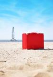 Roter Reisen-Ferien-Koffer auf Strand Lizenzfreies Stockbild