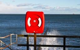 Roter Rettungsgürtel durch die Küste Lizenzfreie Stockfotografie